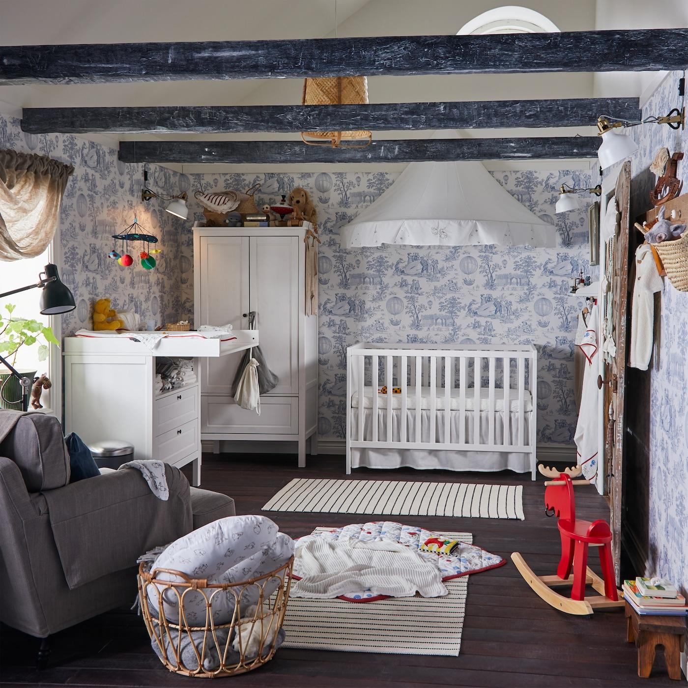Gyerekszoba kék/fehér tapétával, fehér rácsos ággyal és pelenkázóasztallal, fehér gardrób és két fehér/fekete csíkos szőnyeg.