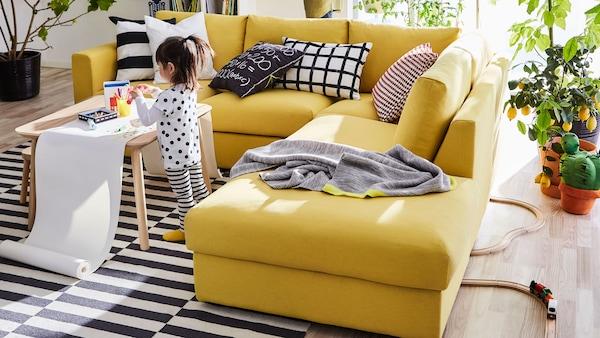 Gyermek rajzol egy nappaliban, sárga kanapé előtt, csíkos szőnyegen.
