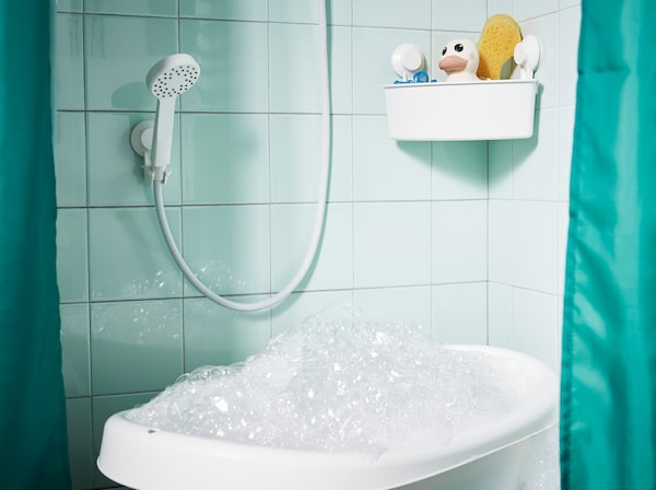 Habbal teli babakád egy zuhanyban, zöld csempével és zöld zuhanyfüggönnyel.