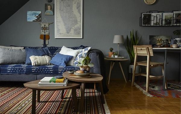 Habitación acogedora con sofá, mesas de centro y una mesa de trabajo con una silla.