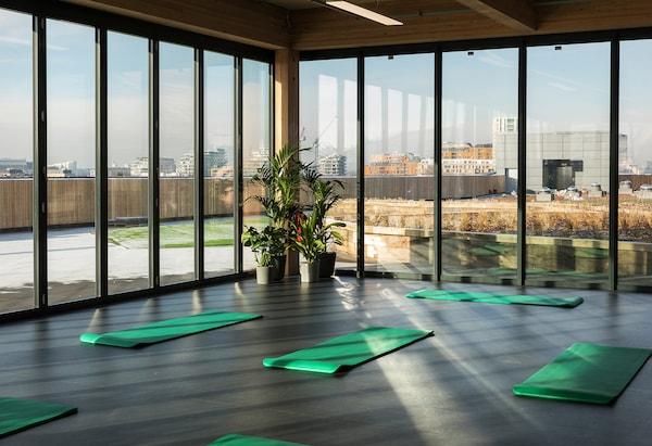 Habitación con esterillas de yoga en el suelo y ventanas de altura completa orientadas hacia una vista de la ciudad.