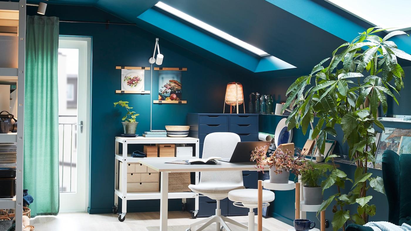 Habitación con un escritorio, una silla giratoria, un escritorio blanco que se puede usar tanto de pie como sentado y plantas frondosas en un soporte.