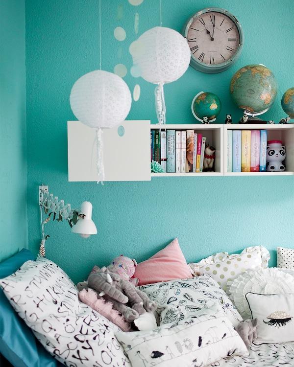 Habitación con una iluminación suave, estantes con libros y almohadas apiladas.