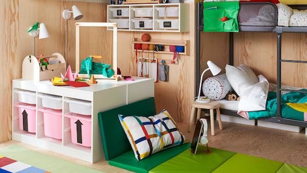 Habitación infantil con litera TUFFING, solución de almacenaje TROFAST y una colchoneta plegable PLUFSIG para sentarse.