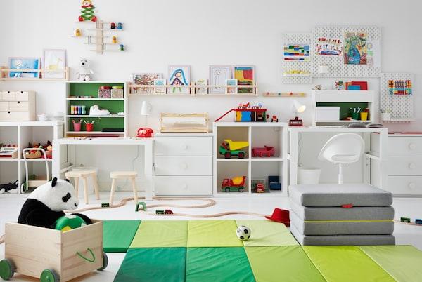 Habitación para niños con juguetes en el suelo, escritorios a los lados y dibujos en repisas de cuadros y pizarrones SKÅDIS en las paredes.