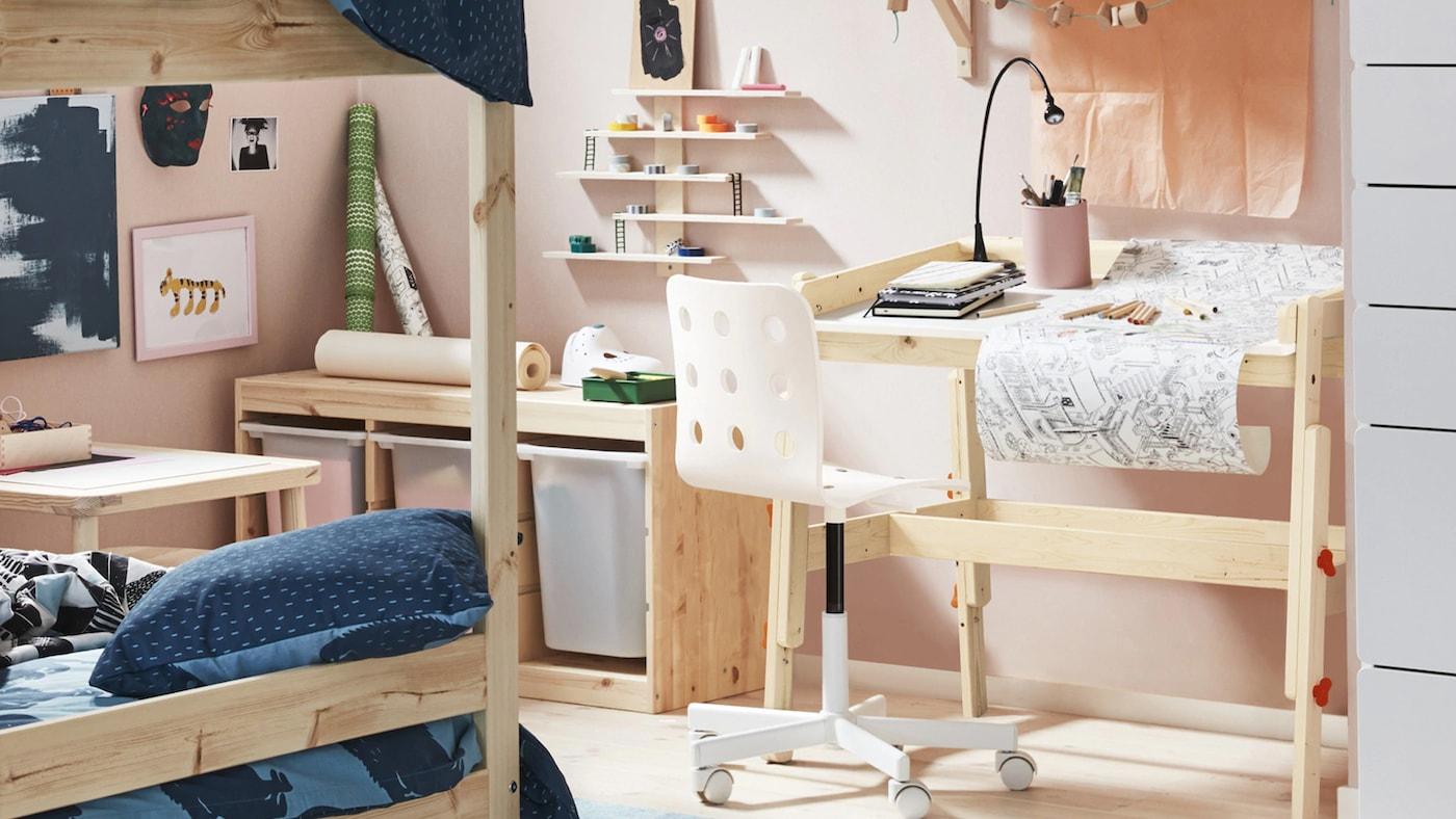 Habitación para niños decorada / pintada en rosa pálido con muebles de madera clara, que incluyen un escritorio y una litera.