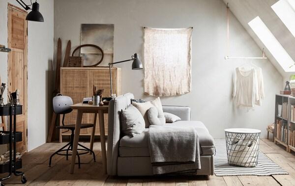 Habitación versátil multiuso con un sofá, una unidad de almacenamiento, mesa de trabajo y silla.
