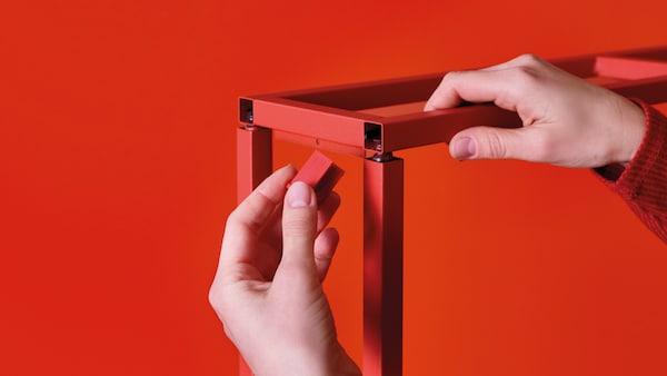 Hände bauen ein rotes Möbelstück zusammen