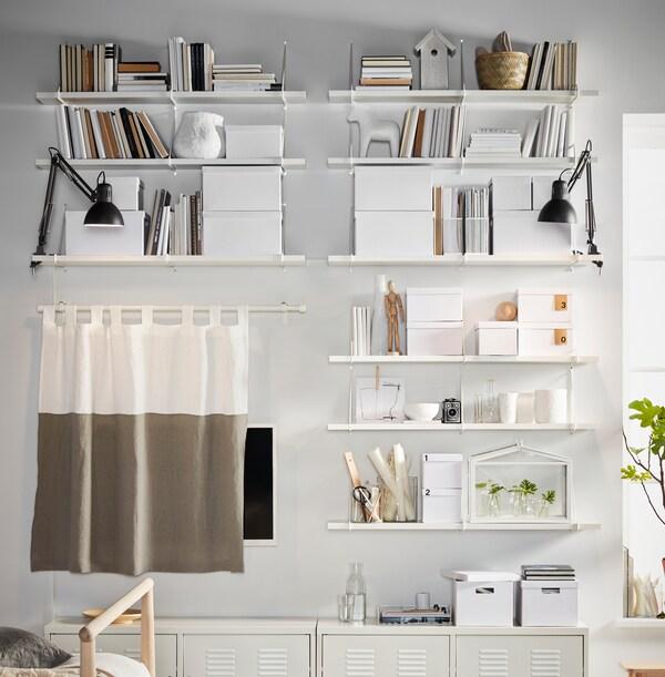 حائط أبيض مليء بالرفوف، وصناديق تخزين TJENA وخزائن IKEA PS، كلها بيضاء وموضوعة بطريقة متناسقة.