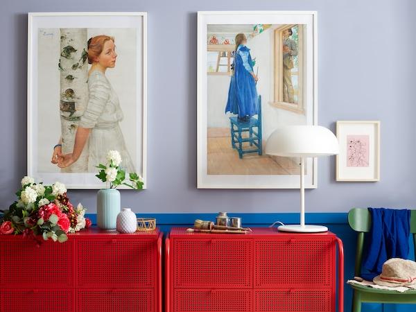 حائط عليه إطارات صور وبعض التخزين باللون الأحمر مع مصباح، ونباتات، ومزهرية STILREN بها زهرة.
