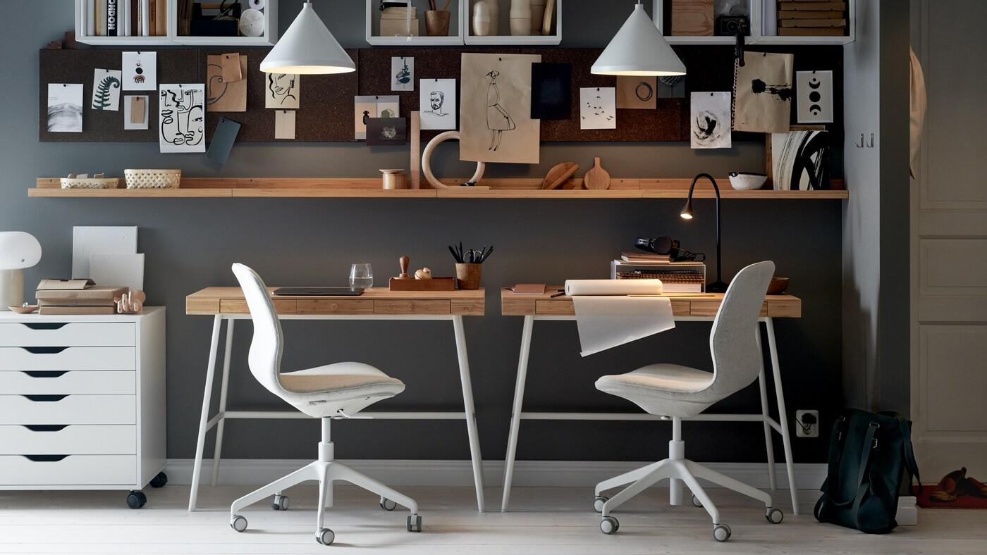 حائط عليه مكتبان LILLÅSEN وكراسي مكتب ووحدة أدراج بيضاء مع رفوف ولوحات ملحوظات ومصابيح معلقة بيضاء.