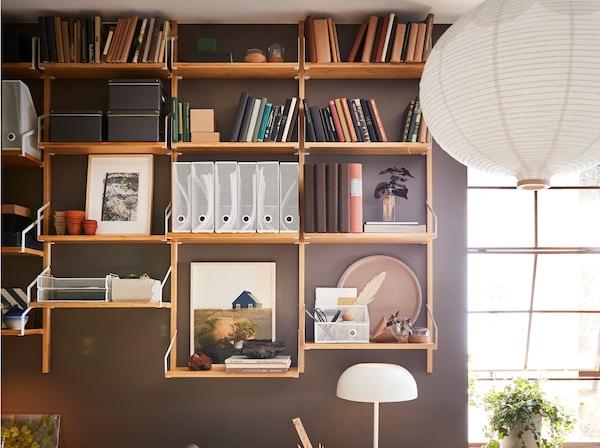 حائط مطلي باللون البني مع مجموعة رفوف مثبتة على الحائط من خشب الخيزران مع كتب وقطع للزينة وحافظات مجلات بيضاء.