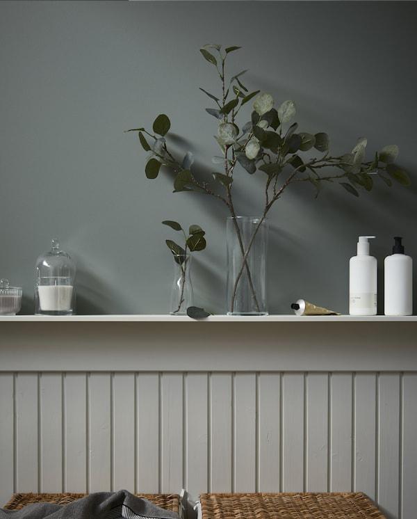 حائط نصف مبلط مع رف حيث توجد قبة زجاجية تغطي شمعة وأغصان زيتون صناعية معروضة في مزهريات زجاج.