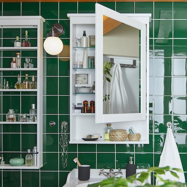 حائط يضم بلاطًا أخضر مثبت عليه خزانة مكشوفة HEMNES بيضاء مزودة بمرآة مرصوص بداخلها منتجات على الرفوف.