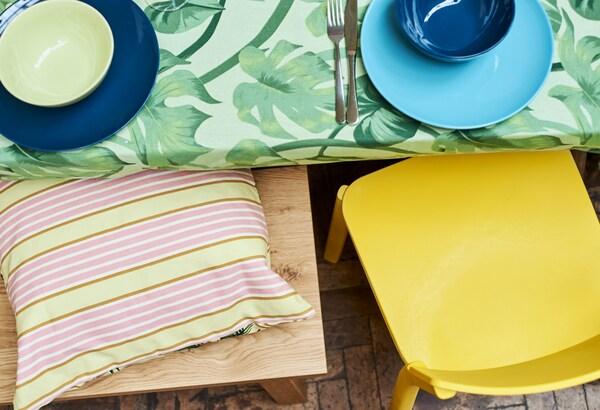 حافة طاولة مغطاة بقماش طباعة ورق شجر أخضر، وكرسي طعام أصفر ومقعد بلوط مع وسادة صفراء مقلمة.