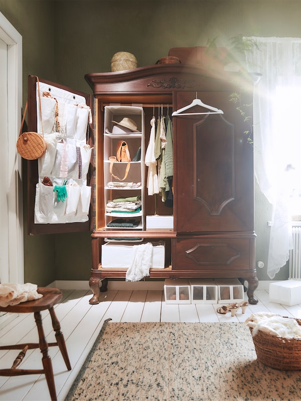 Hagyományos fa tárolószekrény, nyitott ajtóval, benne IKEA ruharendszerezőkkel.