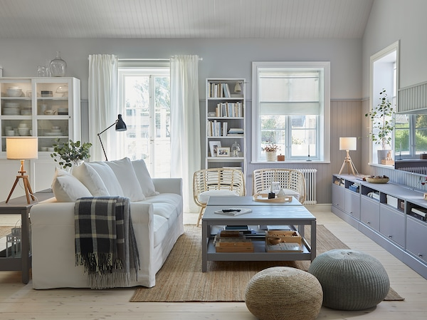 Hagyományos nappali, fehér kanapéval, juta szőnyeggel, két szürke dohányzóasztallal, szürke TV-állvánnyal és két rattan fotellel.