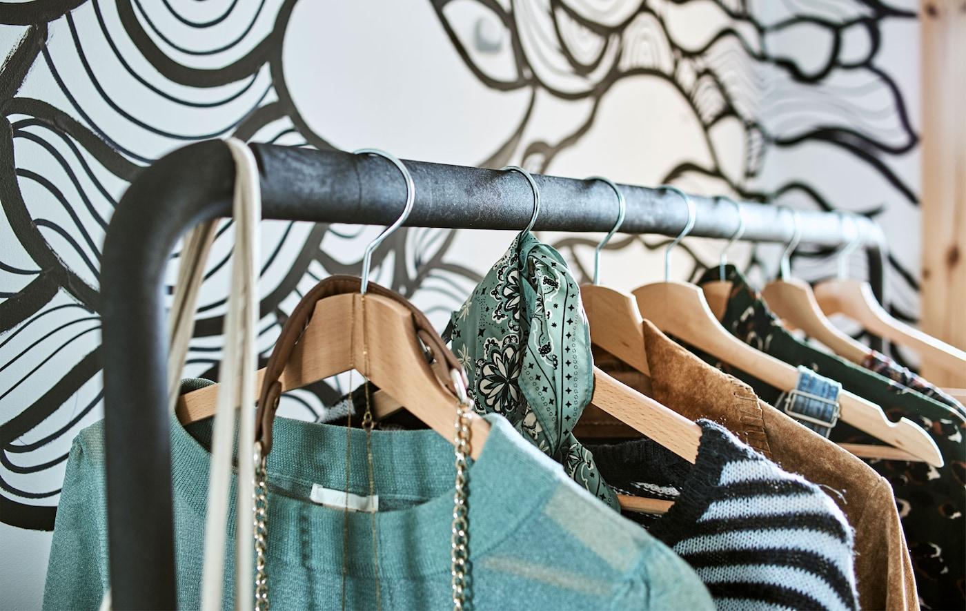 Haine suspendate de umerașe de lemn pe o șină de haine în fața unui tapet cu onduleuri alb-negru.