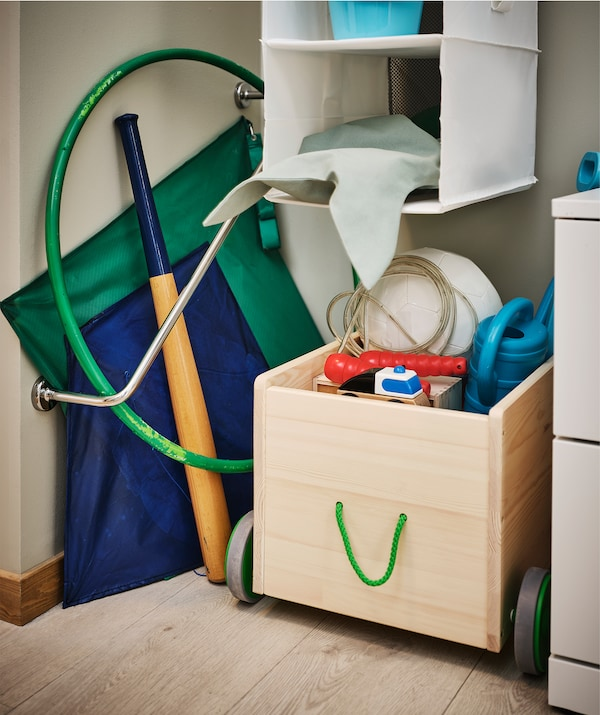 Hallway corner fitted with a diagonal towel rail holding kites, a bat, a hula hoop; a FLISAT box filled with toys beside it.