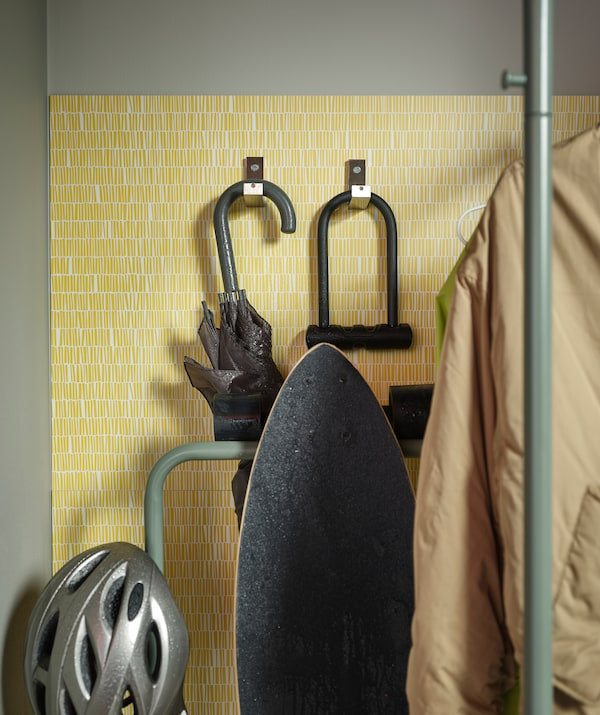 Hallway fitted with LYSEKIL wall panel with hooks for an umbrella, a bicycle lock. A skateboard on a NIKKEBY clothes rack.