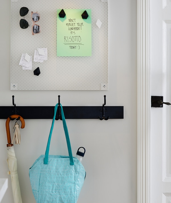 Hallway noticeboard with a remember-your-lunch note. A rack of hooks below, one holding a prepared lunch bag.