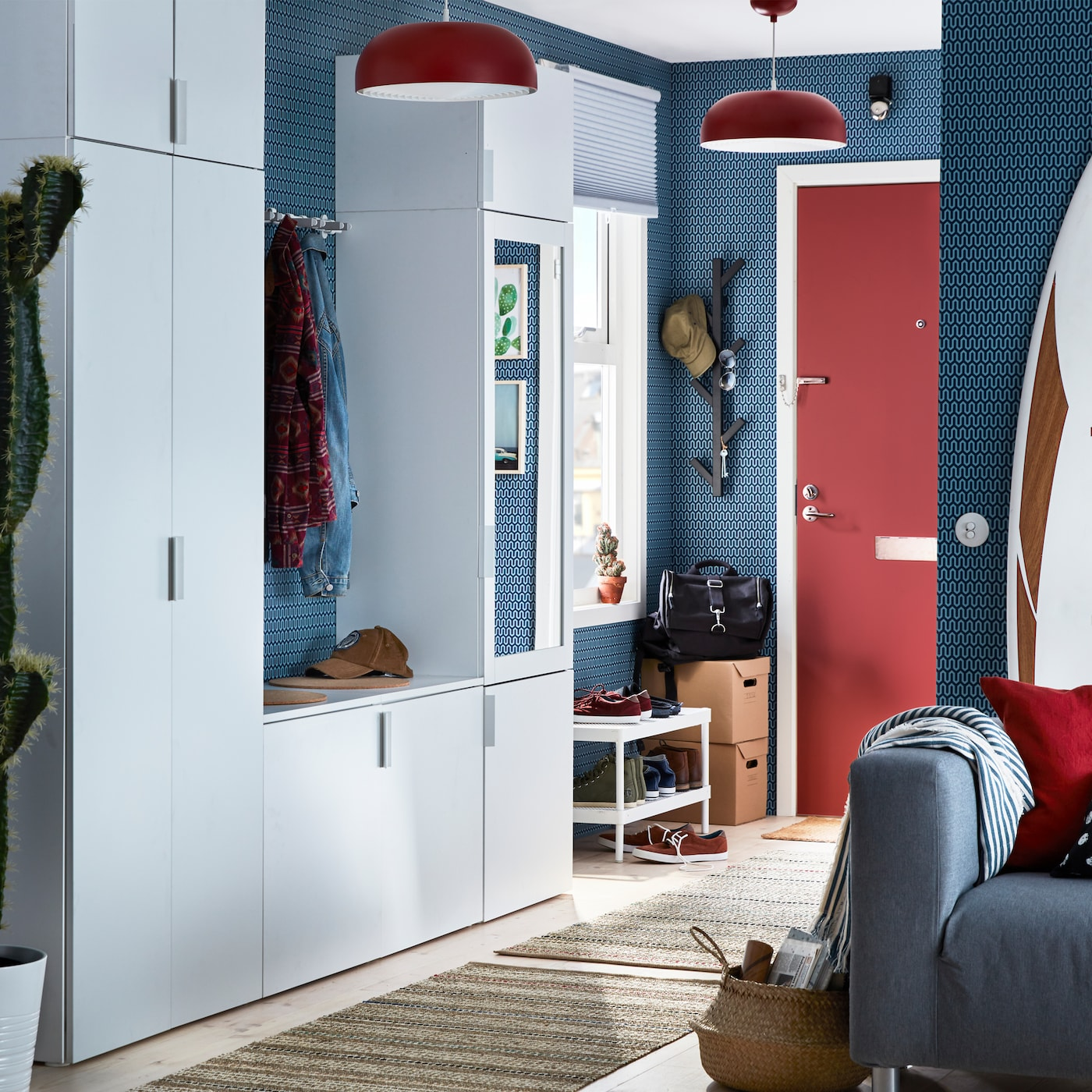 Hallway with a rug leading to a closed door at the rear. A sofa to the right plus PLATSA closets and MACKAPÄR shoe rack to the left.