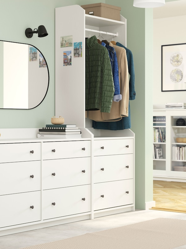 Hallway with wide, white HAUGA chest and wardrobe combo. In the adjacent living room stands a white HAUGA glass-door cabinet.
