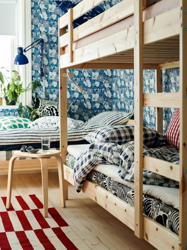 Hálószoba ággyal és emeletes ággyal semleges színekben, virágos tapéta és textíliák különböző színekben és mintákkal.