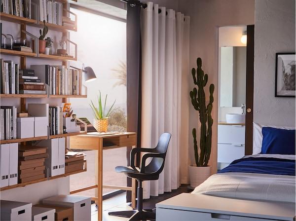 Hálószoba, bambusz íróasztallal az ablak előtt. Fehér és szürke függönyök.
