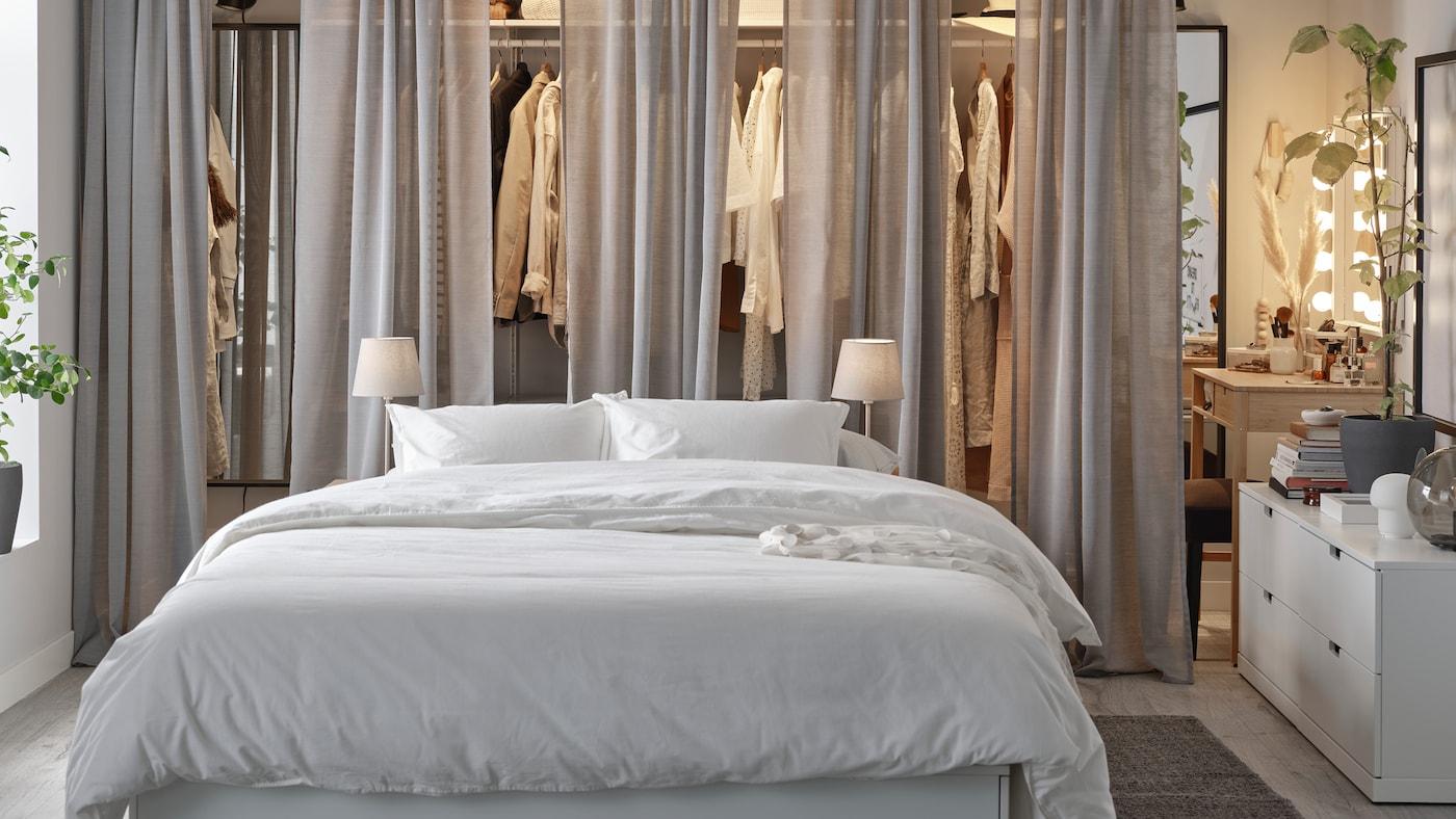 Hálószoba fehér NORDLI ággyal, nyitott BOAXEL gardróbbal, szürke HILJA függönyökkel elöl és NORDLI fiókos szekrényekkel.