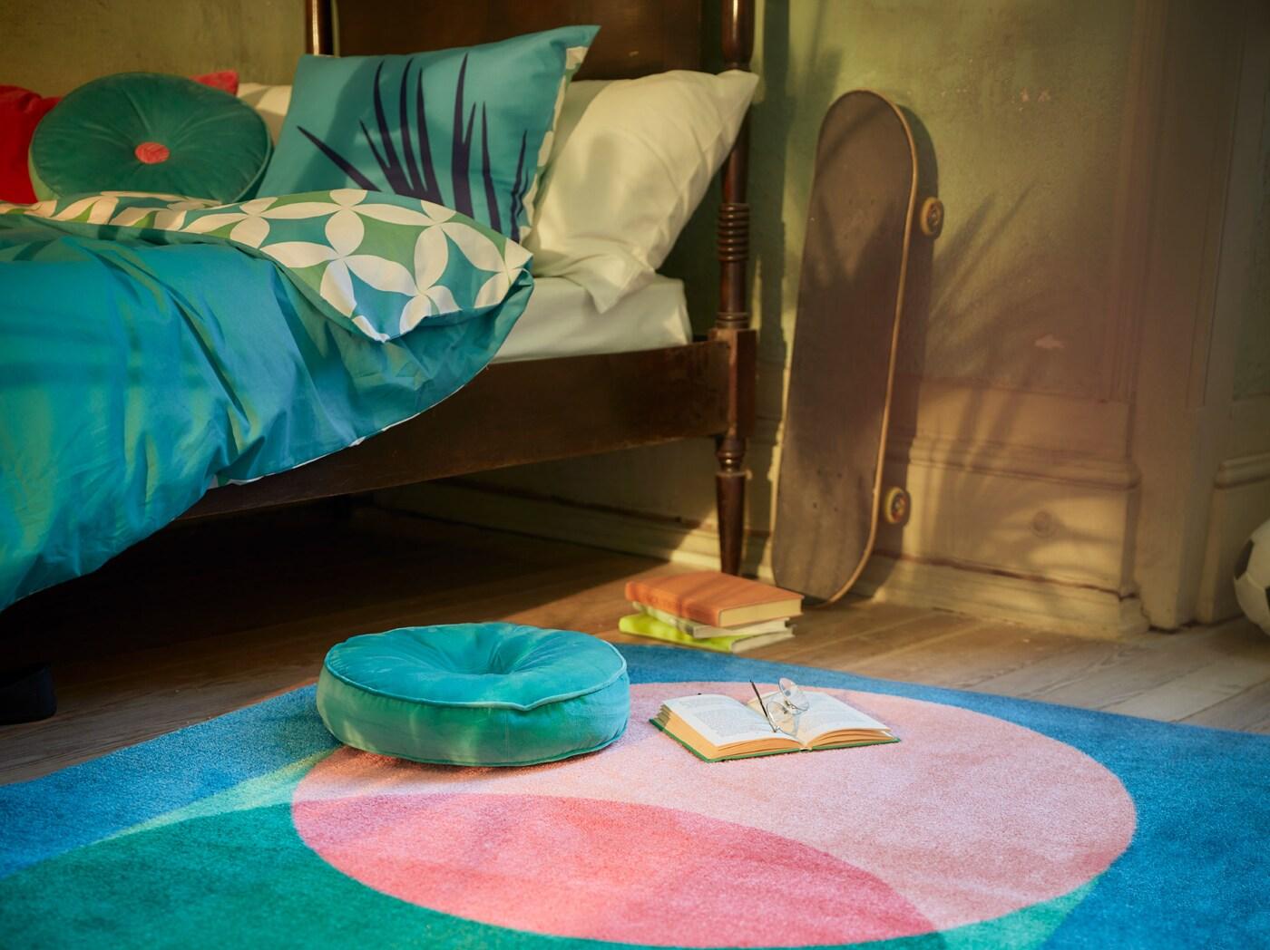 Hálószoba, GRACIÖS textilsorozattal, türkiz tónusokban, paplanhuzattal, mintás szőnyeggel és kerek bársonypárnával.