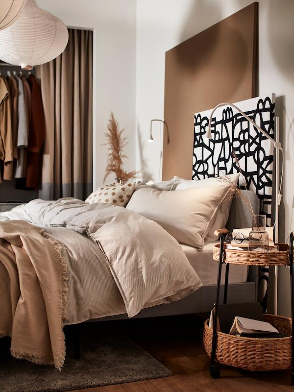 Hálószoba megnyugtató színekben, sok textíliával és egy fejtámlás ággyal.
