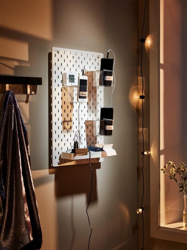 Halványan megvilágított fal, amelyen egy SKÅDIS fali tábla lóg, LÖRBY töltőket, mobiltelefonokat és telefon-kiegészítőket tartalmazó tartókkal.