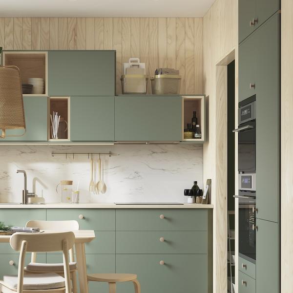 Halványzöld METOD konyha, világos faburkolattal.