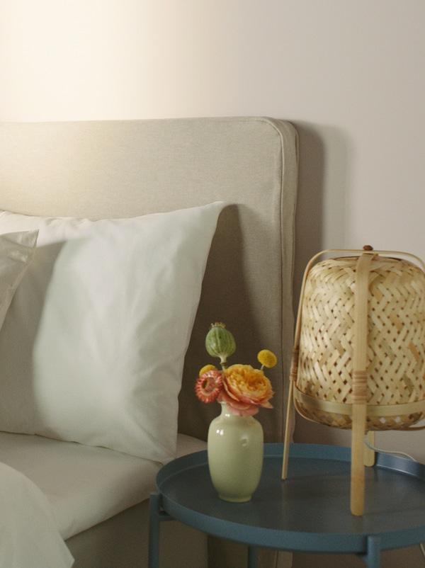 Halvdelen af en sengegavl med en hvid pude. Ved siden af et natbord, hvor der står en lille vase med blomster og en bordlampe i bambus.
