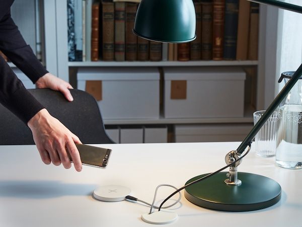 Hand holding a phone over a desktop where the cables of a lamp and a wireless phone charger disappear into the desk.