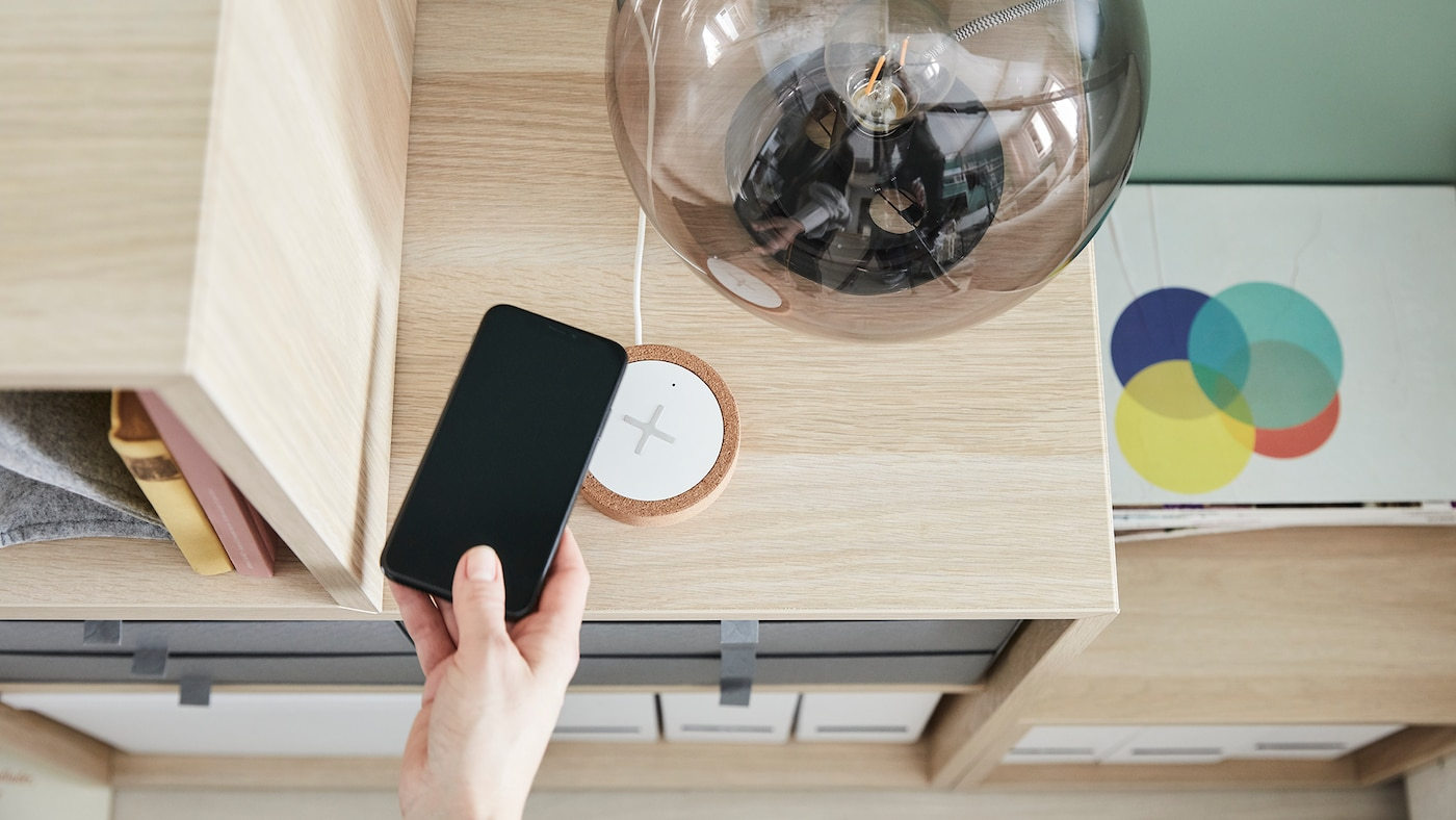 Hand placing a mobile phone onto a wireless charger, situated on top of a storage cabinet.