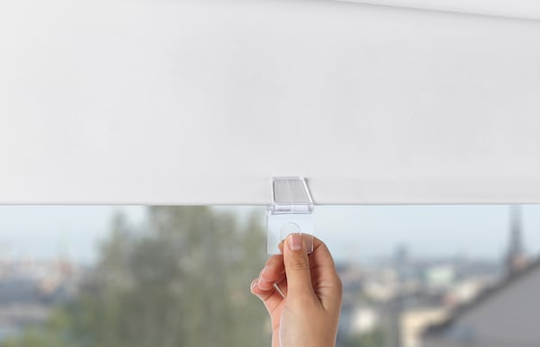 Hand pulling down a blind by the cord.