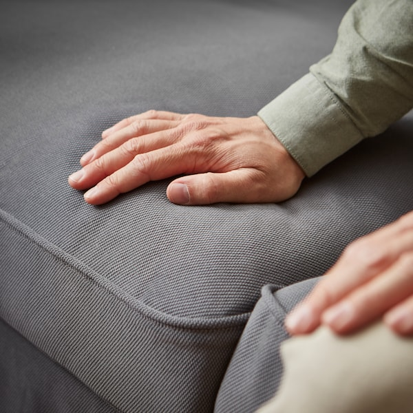 Hand som stryker över tyget på en grå EKTORP soffa.