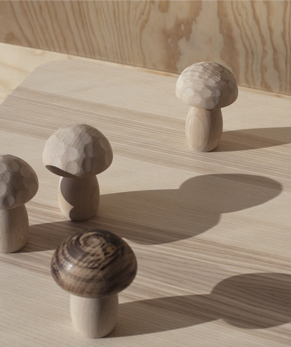 Hand-turned wooden mushroom shapes from the IKEA ANNANSTANS collection standing on a wooden surface.