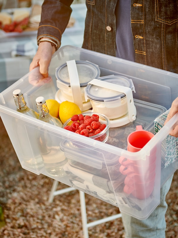 Handen die een SAMLA doos vasthouden gevuld met servies, glazen flessen en voedselbakjes die aan IKEA 365+ icepacks zijn vastgemaakt.