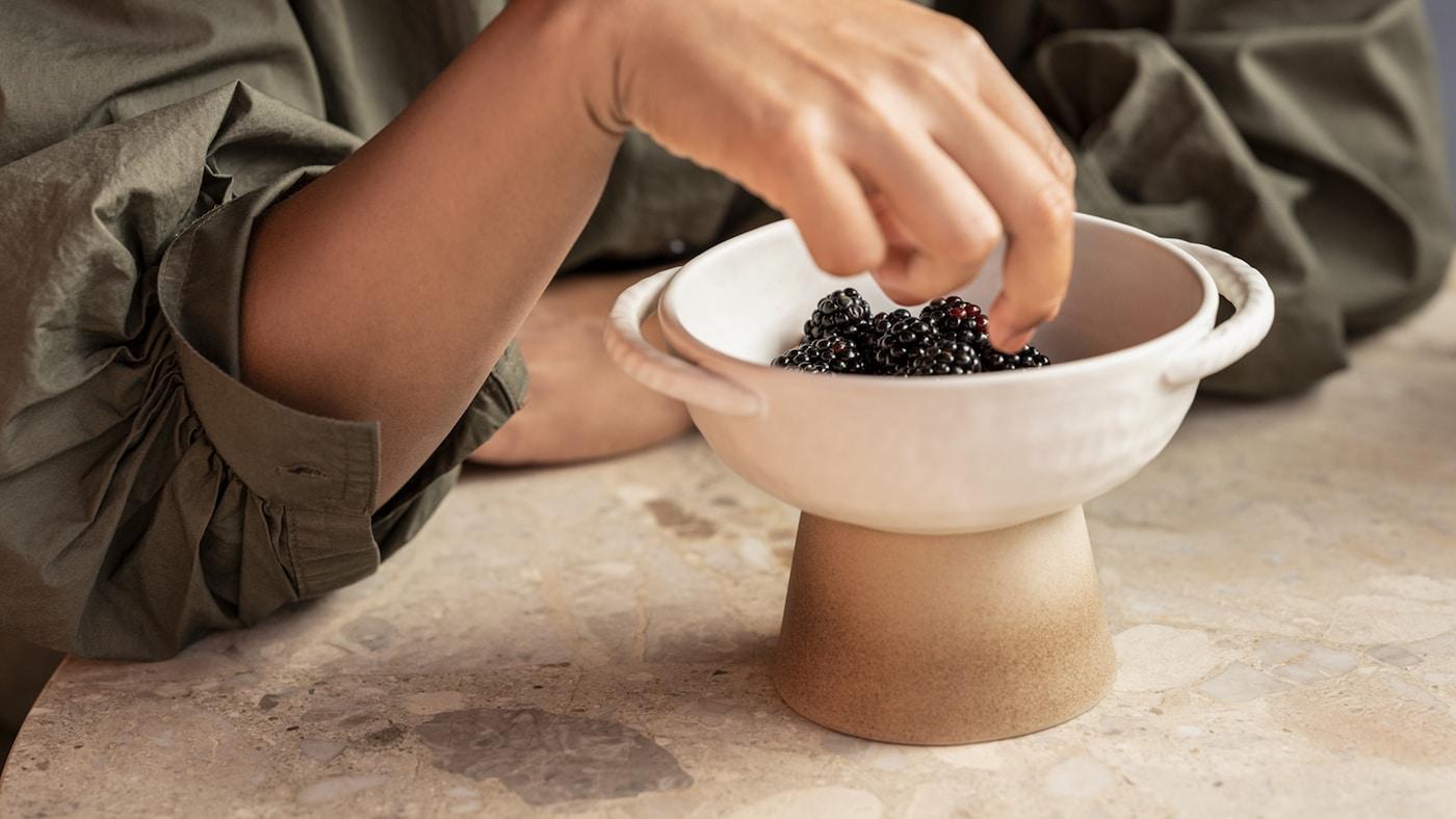 Handen på en kvinna som tar ett mullbär från en handgjord LOKALT keramikskål som står på en marmoryta.