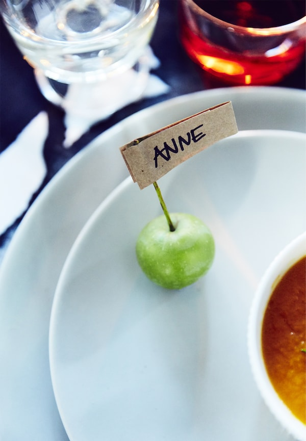 Handgeschriebene Tischkarte auf OFTAST Teller in Weiß, die in einem Apfel steckt