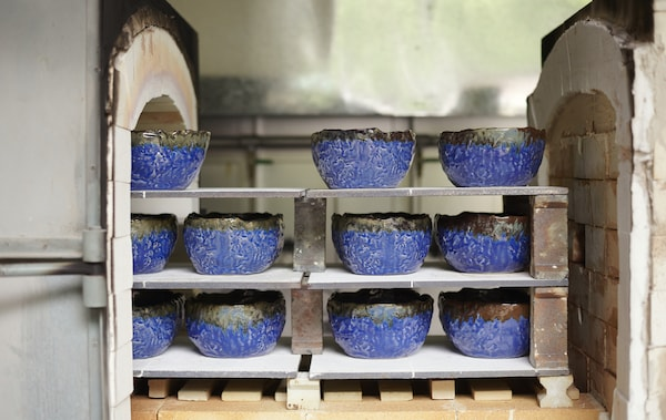 Handmade, irregular blue ceramic bowls from the IKEA ANNANSTANS collection on shelves of a brick kiln.
