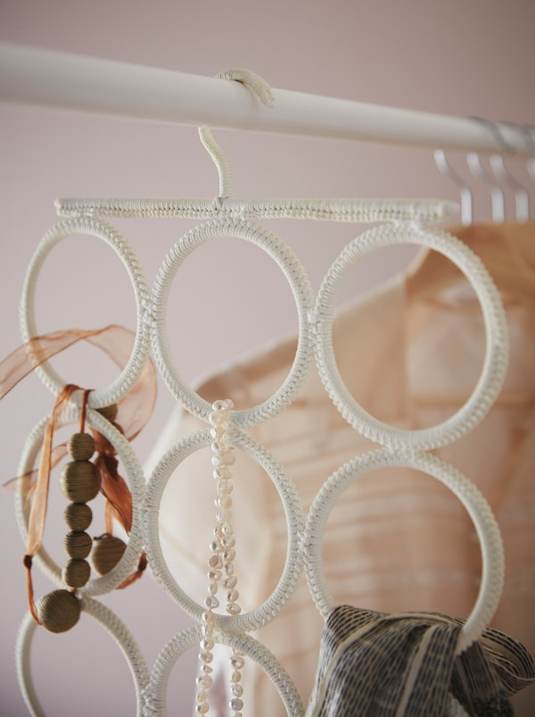 Hanging from a wardrobe rod is a KOMPLEMENT multi-use hanger holding necklaces, a scarf and other accessories.