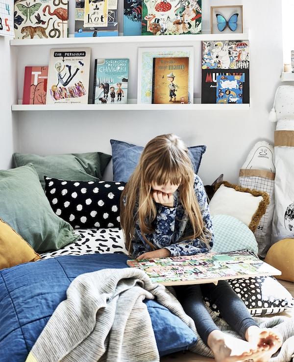 Hania lueskelee sängyllään. Ympärillä on värikkäitä tyynyjä ja peittoja, ja kirjat säilytetään näyttävästi kapealla tauluhyllyllä.