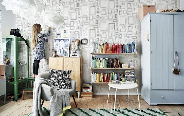 Hania nella sua cameretta arredata con mobili colorati, un tappeto verde e una libreria arcobaleno – IKEA
