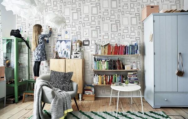 Hania omassa huoneessaan, jossa on värikkäitä huonekaluja, vihreä matto ja värien mukaan järjestetty kirjahylly.