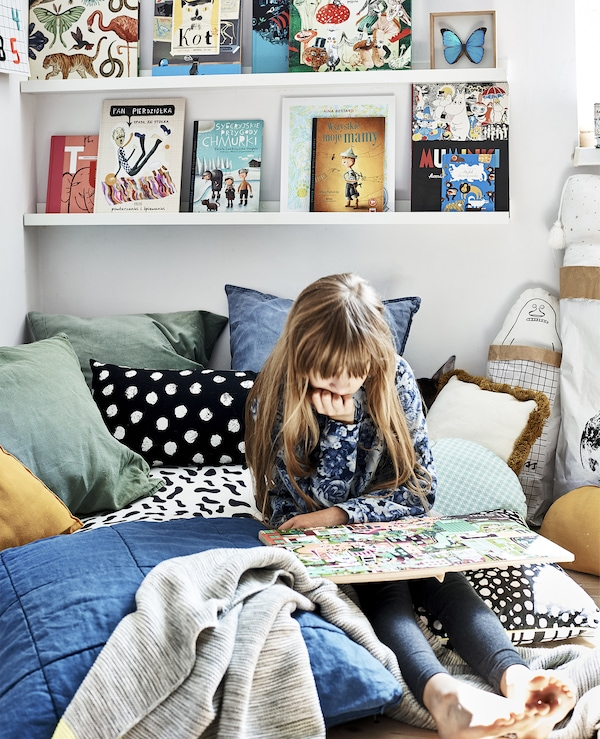 Hania reading on her bed, with colourful textiles and books on a picture ledge.