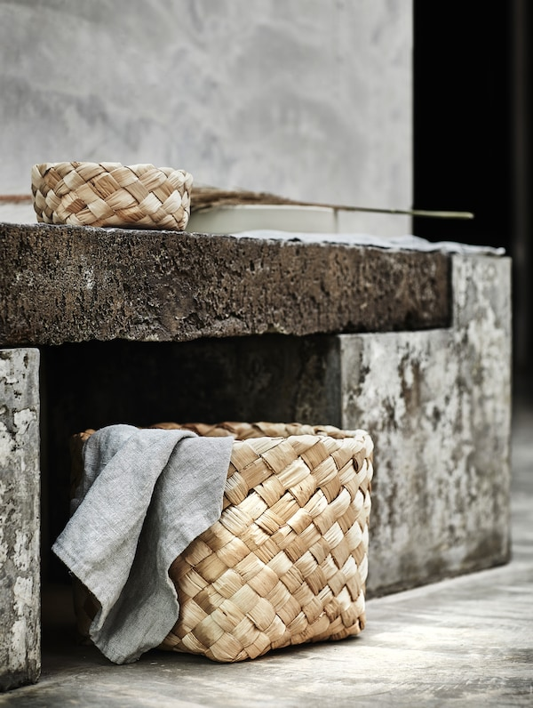 HANTVERK baskets in two sizes placed under and on top of a stone bench. Both made of banana fibre and handwoven in India.